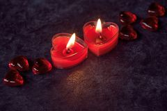 St Valentine day decor. Two red heart shaped candles, St Valentine day decor at the dark background stock photography