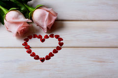 St. Valentine`s Day background with two pink roses and red heart Royalty Free Stock Photography