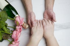 St. Valentine`s Day concept.Marriage of elderly couple.Bottle of wine,pink roses for great romantic evening.Top view. Male and female hands of elderly couple royalty free stock images