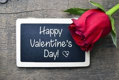 St Valentine`s Day concept.Red rose and chalkboard with text Happy Valentine`s Day on old wooden background. stock images