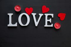 St. Valentine`s day concept. word LOVE lays on the wooden background with red hearts stock photography