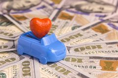 St. Valentine`s Day. Costs for a honeymoon trip by private car. A wedding contract. Concept love for money. Red heart in a blue c Royalty Free Stock Images