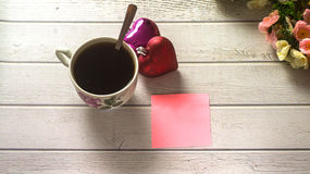 St. Valentine`s day. Cup of coffee with empty love letter on white wooden table Royalty Free Stock Images