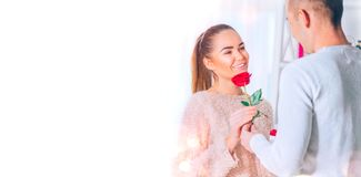 St. Valentine`s Day. Love concept. Young man giving a flower to his girlfriend stock image