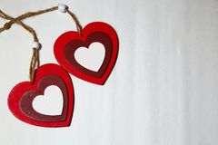 St. Valentine`s Day, love. Two red hearts with bells on a light royalty free stock photos