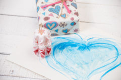St. Valentine`s Day: one carved candle, drawing of heart and gift. Stock Photos
