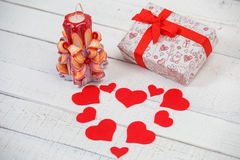 St. Valentine`s Day: one carved candle, hearts from felt and a gift with  red tape. Stock Photos