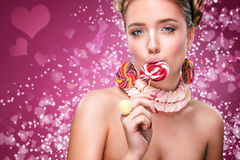 St valentine`s day, Portrait beautiful young sexy blond girl taked red lollipop. On pink background with hearts. Young woman with candy on pink bakground Royalty Free Stock Photography