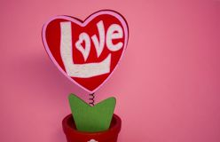 St. Valentine`s Day. Red wooden heart with the inscription `love`. On a spring with a clothespeg. On a pink background. St. Valentine`s Day. Red wooden heart stock photography