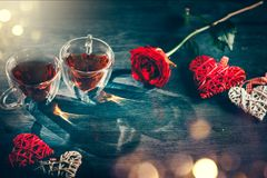 St. Valentine`s Day scene. Valentine heart shaped tea cups with red hearts rattan decor and red rose on wooden background. Dating royalty free stock photos