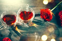 St. Valentine`s Day scene. Valentine heart shaped tea cups with red hearts rattan decor and red rose on wooden background. Dating royalty free stock image