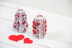 St. Valentine`s Day: two carved candles and  felt hearts as love symbol. Stock Photo
