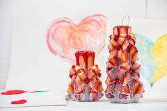 St. Valentine`s Day: two carved candles of orange color against the background  pink heart. Stock Image