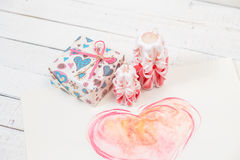 St. Valentine`s Day: two carved candles of pink color, the packed gift and big heart. Royalty Free Stock Image
