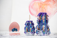 St. Valentine`s Day: two carved candles of violet color against the background  pink heart. Stock Photos