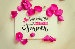 St Valentine`s Day vintage composition of greeting note. With hand drawn lettering  and rose petals on wooden table Stock Images