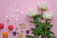 St Valentine`s Day vintage composition of white roses, macarons. Chocolate hearts and hand drawn love quote on pink background Royalty Free Stock Photography