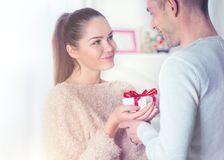 St. Valentine`s Day. Young man giving a gift to his girlfriend royalty free stock photo