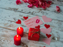 St Valentine`s decor on wooden background, red candles with red gift and hearts from craft paper. Stock Image