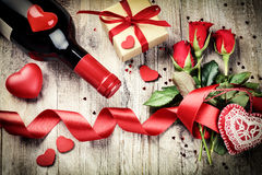 St Valentine's setting with red roses bouquet, present and red w Stock Photos