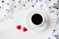 St Valentines day background - cup of coffee, blank love card and two heart shaped candies Stock Photos