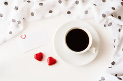 St Valentines day background - cup of coffee, blank love card and two heart shaped candies Royalty Free Stock Image