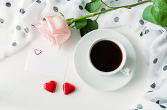 St Valentines day background - cup of coffee, rose, blank love card and two red heart shaped candies Stock Image