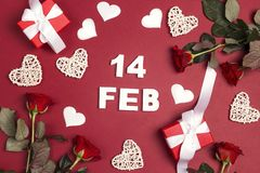 St. Valentines Day background with date, gifts, rose flowers and decorative hearts on red. Top down composition royalty free stock photo