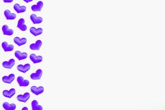 St Valentines day background. Purple textile hearts border on the white wooden background, space for text. St Valentines day background. One side border of royalty free stock image