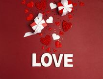 St. Valentines Day background word love, gifts and decorative hearts on red. Top down composition royalty free stock photo