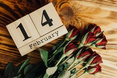 St. valentines day minimal concept on wooden background. Red roses and wooden caledar with 14 february on it. Copy space Stock Images