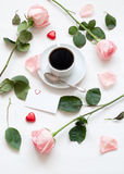 St Valentines day still life - cup of coffee, peach roses, blank love card and heart shaped candies. Love romantic background Stock Image