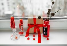 St. Valentines Day still-life with red heart. Red candles, plastic heart and gift-box with ribbon are on the windowsill. St. Valentine`s Day still- life stock images