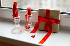 St. Valentines Day still-life with red heart. Red candles, plastic heart and gift-box with ribbon are on the windowsill. St. Valentine`s Day still- life royalty free stock photo