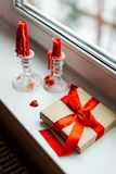 St. Valentines Day still-life with red heart. Red candles, plastic heart and gift-box with ribbon are on the windowsill. St. Valentine`s Day still- life royalty free stock photography