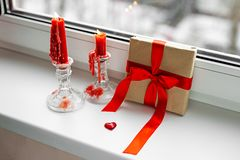St. Valentines Day still-life with red heart. Red candles, plastic heart and gift-box with ribbon are on the windowsill. St. Valentine`s Day still- life stock photography