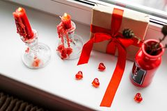 St. Valentines Day still-life with red heart. Red candles, plastic heart and gift-box with ribbon are on the windowsill. St. Valentine`s Day still- life royalty free stock image