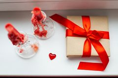 St. Valentines Day still-life with red heart. Red candles, plastic heart and gift-box with ribbon are on the windowsill. St. Valentine`s Day still- life royalty free stock photos
