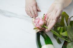 St.-Valentinsgruß ` s Tageskonzept Frau, die für Valentinstagblumenstrauß von Rosen anwesend erhält Champagne für romantisches Ab lizenzfreie stockbilder