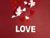 St.-Valentinsgruß-Tageshintergrundwortliebe, Geschenke und dekorative Herzen auf Rot lizenzfreies stockfoto