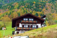 Traditional Chalet house and Alps mountains in Salzkammergut. St.Wolfgang, Austria - October 24, 2017: Traditional Chalet house and Alps mountains in Royalty Free Stock Photo