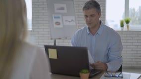 Stały męski kierownik wyższego szczebla wiek średni przeprowadza wywiad młodego specjalisty biurową pracę życzliwa drużyna 4K zbiory wideo