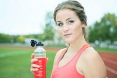 Stażowa młoda kobieta napoju butelka Zdjęcia Stock