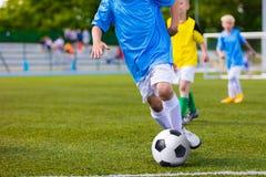 Stażowy i futbolowy dopasowanie między młodości piłki nożnej drużynami Młode chłopiec kopie mecz piłkarskiego Fotografia Royalty Free