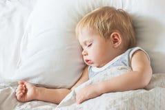 Söta Little Boy som sover på säng Fotografering för Bildbyråer