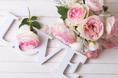 Söta rosa rosblommor och ordförälskelse på vit målade trä Arkivbild