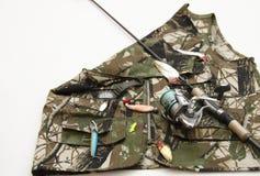 Staaf met spoel en visserijtoebehoren op camouflagejasje Royalty-vrije Stock Afbeeldingen