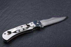 Staal die mes met een open blad op een steenoppervlakte vouwen Staalwapens Het concept wapen, de jacht of misdaad stock foto's