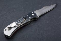 Staal die mes met een open blad op een steenoppervlakte vouwen Staalwapens Het concept wapen, de jacht of misdaad royalty-vrije stock foto