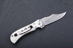 Staal die mes met een open blad op een steenoppervlakte vouwen Staalwapens Het concept wapen, de jacht of misdaad royalty-vrije stock foto's